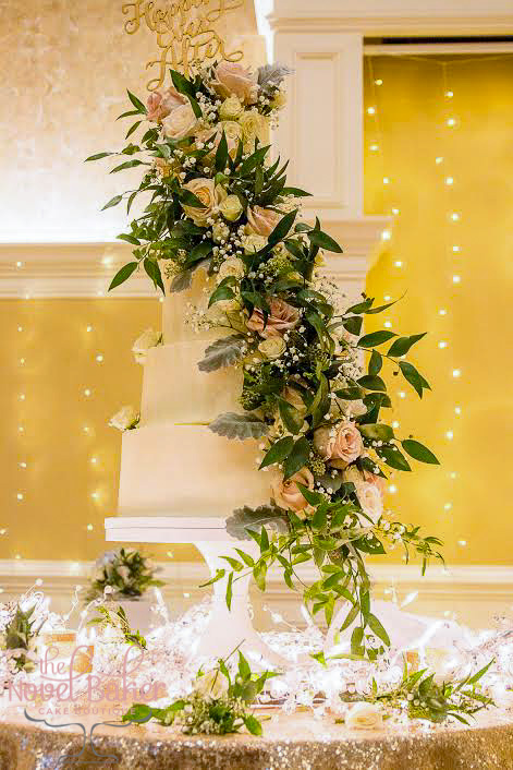 Four-tiered buttercream wedding cake with dramatic arrangement of roses and lush greens