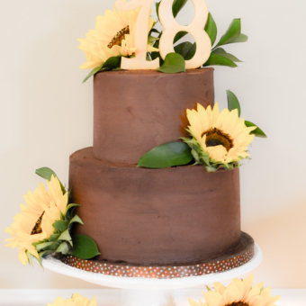 Chocolate 2 Tier Cake with fresh sunflowers and fondant 18 Topper on a Sweet Table of Cookies
